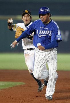 Munenori Kawasaki of Japan's Fukuoka SoftBank Hawks chases Chae Tae-in of South Korea's Samsung Lions back to first base during the fifth inning of their championship of 2011 Asia Series baseball game at the Taichung Intercontinental Baseball Stadium