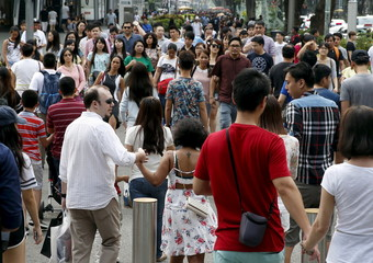 People cross a road in Singapore's shopping district Orchard Road