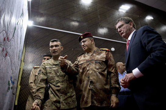 U.S. Defense Secretary Ash Carter and Iraqi Lt. Gen. Abdul Amir al-Lami look over diagrams and maps at the Combined Joint Operations Center in Baghdad