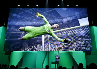 """U.S. national soccer team's goalkeeper Hope Solo's image is shown on the screen as David Rutter, vice president and general manager of EA Sports FIFA, introduces the video game """"FIFA 16"""" in Los Angeles"""