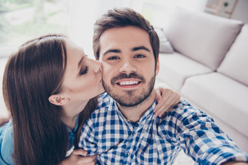 Selfie with my half. Love you. Attractive young couple is taking a selfie on camera, girl kisses her boyfriend, they are indoors at home