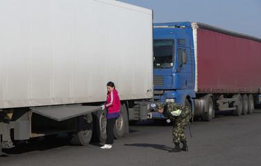 A Belarussian border guard checks a truck at the border check point near Brest