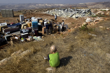 Jewish settler boy watches as people sort their belongings after Israeli authorities demolished three buildings in unauthorized Jewish hilltop outpost of Migron