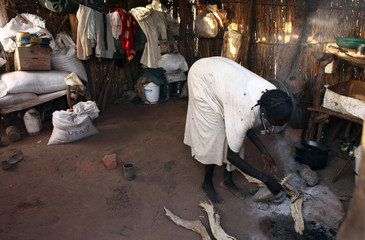 A refugee prepares a cooking-fire inside her makeshift shelter at the Yida refugee camp in Yida