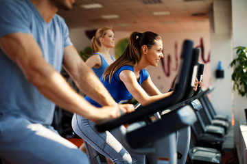 Young woman and man warming up on bikes in the gym