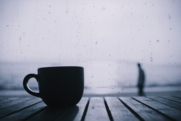 Cup of coffee on wooden table in the morning with rain drops on glass, cooling tone image