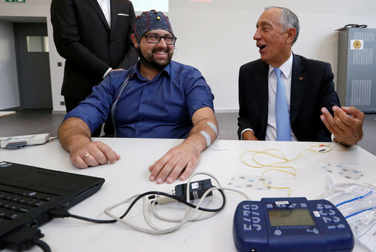 President of Portugal Marcelo Rebelo de Sousa receives electrodes on his arm before a demonstration of Neurosciences performed by scientist Serafeim Perdikis at the Campus Biotech in Geneva