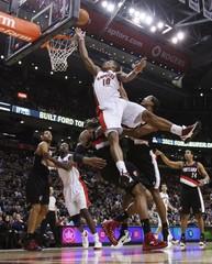Raptors DeRozan goes to the basket against Trail Blazers Aldridge and Cunnignham during their NBA basketball game in Toronto