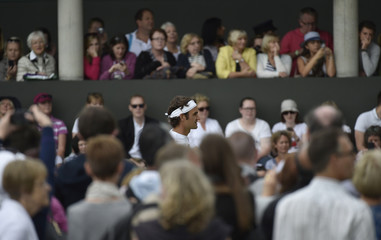 Roger Federer of Switzerland is watched by spectators during a practice session at the Wimbledon Tennis Championships in London