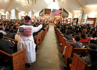 Minister Ann Breedlove waves an American flag during the Martin Luther King Jr. Commemorative Service at Ebenezer Baptist Church in Atlanta, Georgia