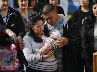 One of the smallest surviving babies born is held by her parents during a news conference announcing the baby's discharge in Los Angeles