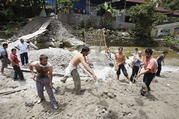 Tourists and local residents collect sand and stones to prepare barricades to contain the water of the river that is flooding the town of Machu Picchu