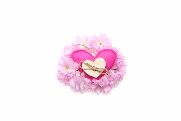 Handmade pink cloth heart placed in wreath of sakura flowers