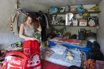 Activist Sokol brushes her hair as she stands in the car shed that serves as home for the Voina activists in Moscow