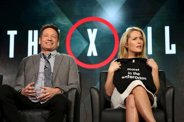 """Actor David Duchovny laughs as actress Gillian Anderson, both of """"The X Files"""", holds up a shirt during the Fox Network presentation at the Television Critics Association (TCA) winter press tour in Pasadena, California"""