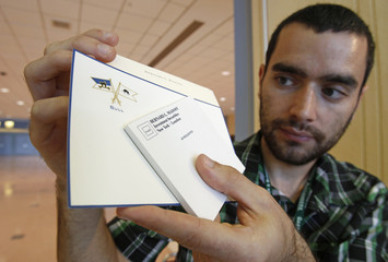 Mike Burd shows monogramed stationary formerly owned by convicted schemer Brnard Madoff, which he won at an auction at the Miami Beach Convention Center