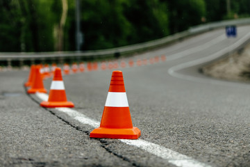 bright orange traffic cones on dark asphalt serpentine mountain roads