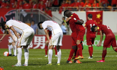 China's players react as Hong Kong's players celebrate after drawing in their World Cup qualifying soccer match in Hong Kong, China