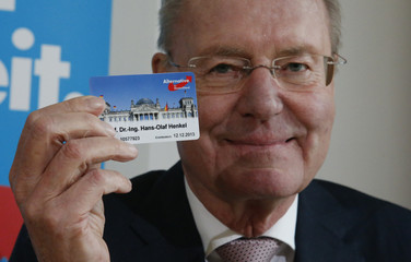 Euro-sceptic former head of the Federation of German Industry Henkel poses with his membership card for Alternative for Germany party in Berlin