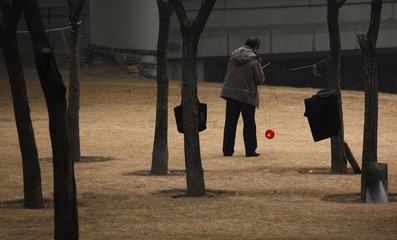 A man spins a top using strings attached to sticks, in a park located underneath a main road in central Beijing