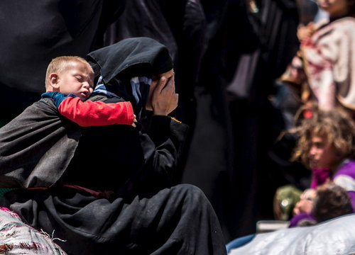 A woman reacts as she rests from walking back to Tel Abyad town