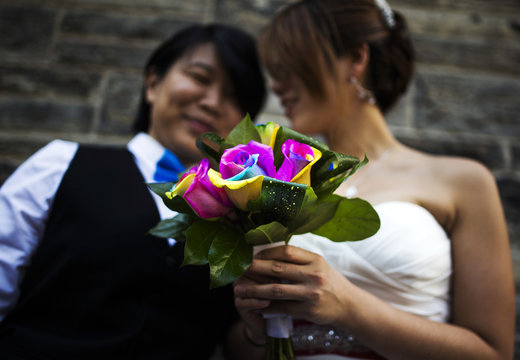 """Lee and Chang Ho hold a rainbow-coloured bouquet of flowers, before they take part in the """"Celebration of Love"""", a grand wedding where over 100 LGBT couples got married, at Casa Loma in Toronto"""