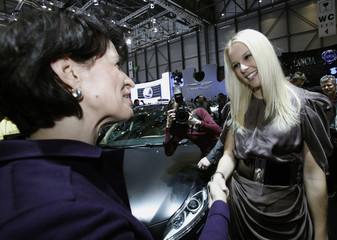 Miss Switzerland Faeh shakes hand with Swiss President Leuthard during the official opening of the 80th Geneva Car Show at the Palexpo in Geneva
