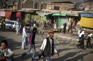 An Afghan man carries bread for sale on his head at a market in Kabul