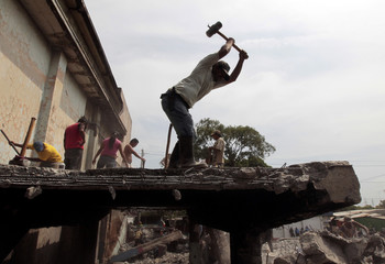A man removes scrap iron that will be sold to recycling companies from the ruins of a building damaged by a 1972 earthquake in the old centre of Managua