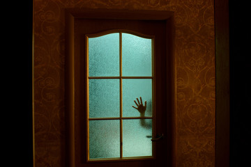 The child's hand through the glass door in the apartment. Green light from the room. Fear.