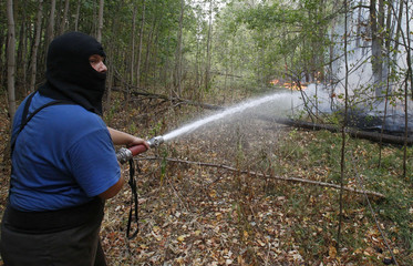 A firefighter works to extinguish forest fire outside the town of Lukhovitsy southeast of Moscow