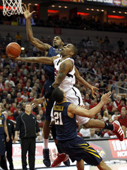Uni of Louisville's Chris Smith fights to get his shot off under pressure from West Virginia Uni's Joe Mazzulla and John Flowers during their NCAA basketball game in Louisville, Kentucky
