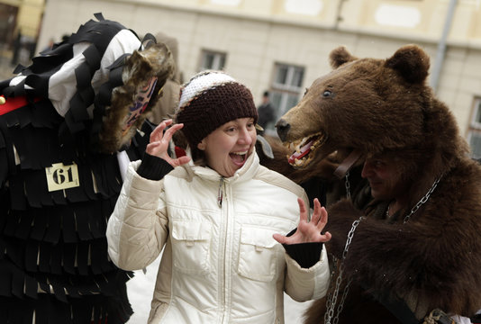 A woman reacts as she is surrounded by masked characters during the Lole Parade in the Transylvanian town of Sibiu