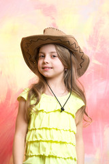 child, little smiling girl in cowboy hat on colorful background