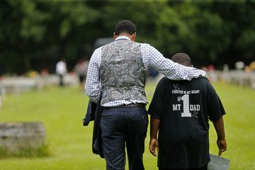 Family attorney Justin Bamberg comforts Na'Quincy son of Alton Sterling at the conclusion Alton's burial at the Mount Pilgrim Benevolent Society Cemetery in Baton Rouge