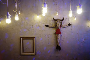 A goat soft toy hangs beside an empty picture frame as decoration in a bar in the Moabit district in Berlin