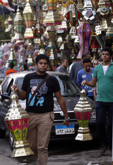 """A man carries a traditional Ramadan lantern known as """"fanous"""" in front of a market stall ahead of the holy fasting month of Ramadan in Cairo"""