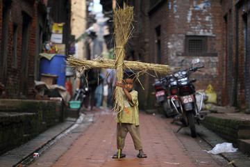 A boy holds an effigy of demon Ghantakarna, which will be set on fire to symbolize the destruction of evil, during the Ghantakarna festival in Bhaktapur