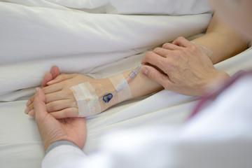 Medical doctor holing patient's hand and comforting her