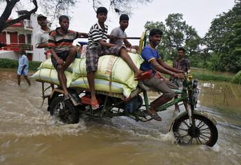 Volunteers transport relief supplies on motor rickshaw through flood waters at Howrah district in West Bengal