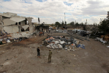 People stand near damaged aid supplies after an airstrike on Tuesday on the rebel held Urem al-Kubra town