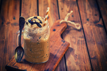 Iced coffee with ice cream and chocolate sauce in a jar