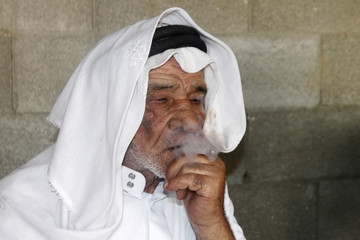 Assad Zaghal, father of Salam, a Palestinian who killed an Israeli settler in the occupied West Bank on Tuesday, smokes during an interview in Shweikeh