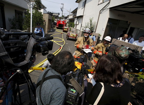 A spokesperson from Tokyo Fire Department speaks to the media in front of the site where a light plane went down in a residential area and burst into flames, in Chofu