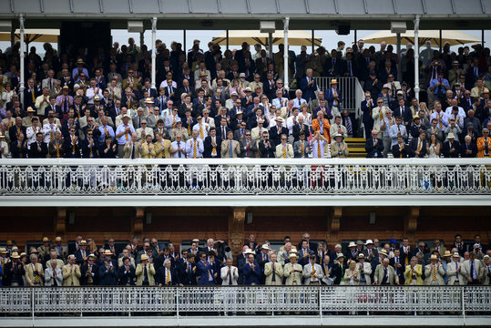 Members on the pavilion balconies applaud England's Root as he leaves the field during the fourth day of the second Ashes test match at Lords cricket ground in London
