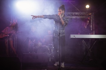 Male singer performing on stage during music festival