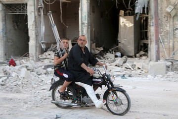 A man with a leg cast rides a motorcycle though a damaged site after what activists said was an airstrike by forces loyal to Syria's President Bashar al-Assad in Old Aleppo, Syria