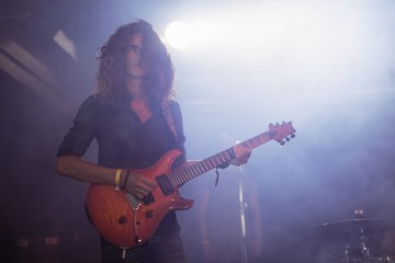 Male guitarist performing with curly hair at nightclub