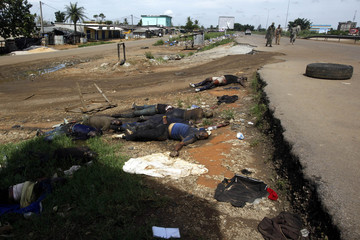 Troops loyal to Ivory Coast presidential claimant Ouattara walk past bodies in Ivory Coast's main city Abidjan
