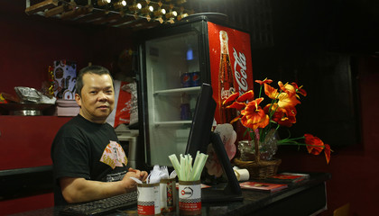 Kwan Chan poses for a photograph at his workplace, Chasing Dragon, in the London constituency of Brent Central